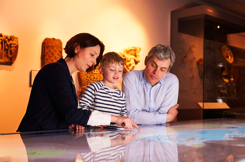 a child looks at a map while the mother explains and the father observes